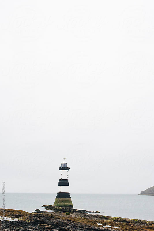 lighthouse  on an overcast day  by Léa Jones for Stocksy United