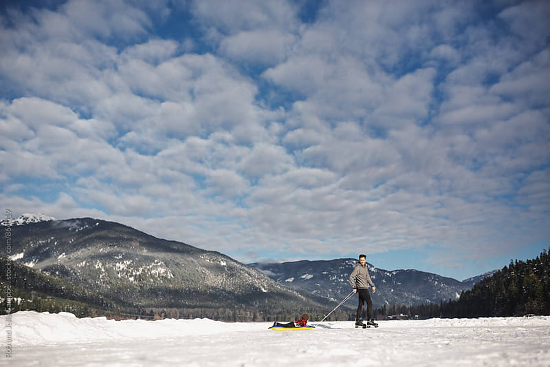 Active young dad pulling son on sled on frozen lake in winter by Rob and Julia Campbell for Stocksy United