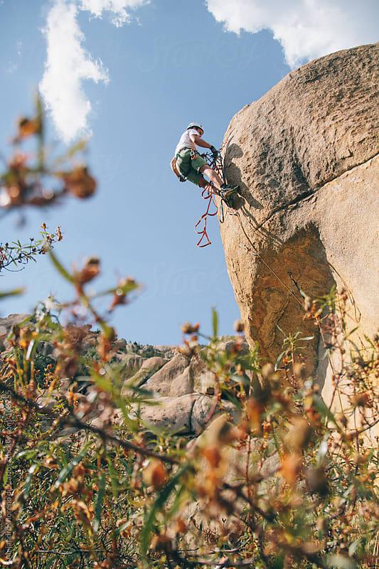 Young man climbing a rock wall. Aid climbing by Alejandro Moreno de Carlos for Stocksy United