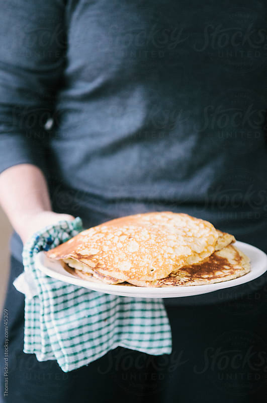 Woman holding a plate of freshly made pancakes, New Zealand. by Thomas Pickard for Stocksy United