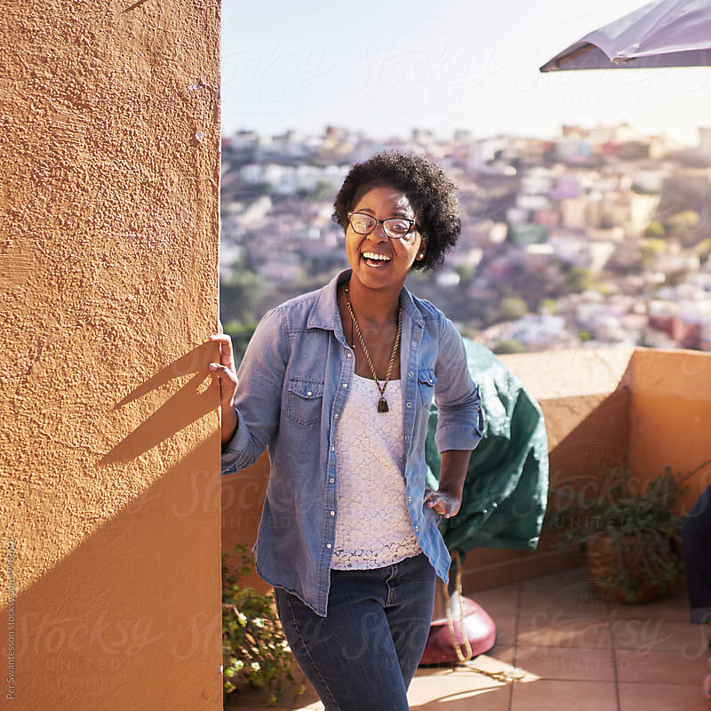 Young happy black woman on a sunny patio by Per Swantesson for Stocksy United