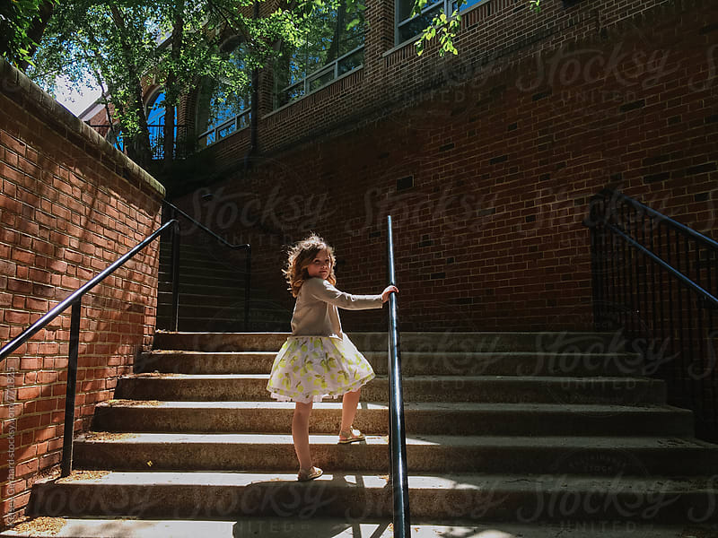 A young girl in a dress stands in a shadowy, light-filled stairwell outdoors. by Kelsey Gerhard for Stocksy United