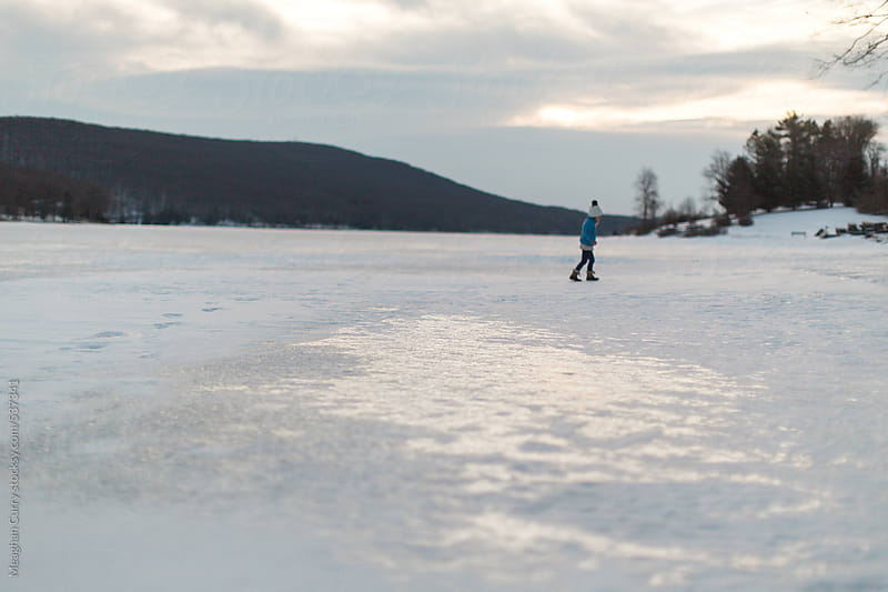 a kid walking on a frozen lake at sunrise by Meaghan Curry for Stocksy United