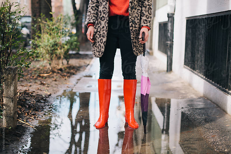 Stylish woman standing in the puddle  by VeaVea for Stocksy United