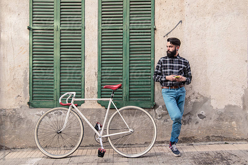 Portrait of hipster with a smartphone and a fixed bicycle by Bisual Studio for Stocksy United
