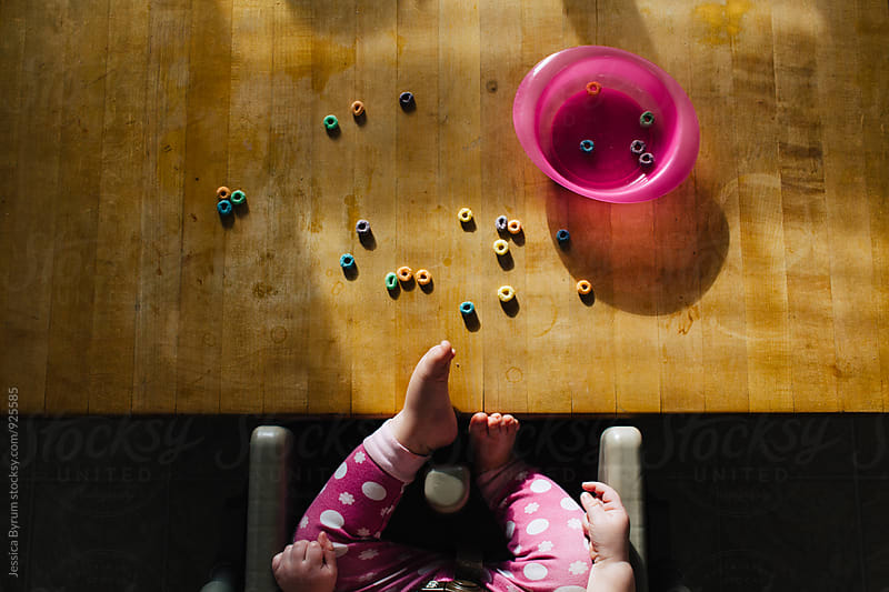 Toddler sitting at table in high chair eating cereal by Jessica Byrum for Stocksy United