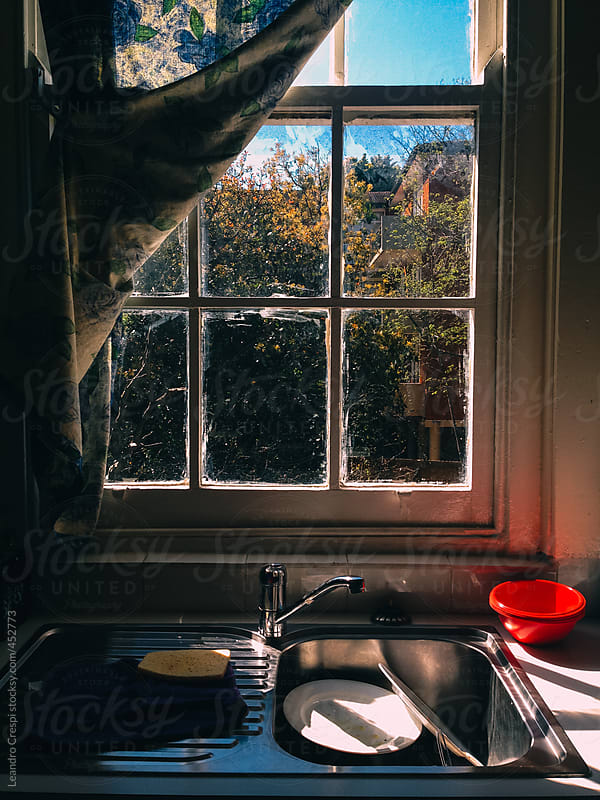 Dirty dishes in a kitchen sink by Leandro Crespi for Stocksy United