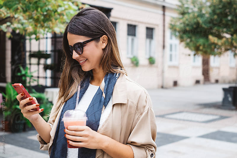 Pretty Woman Typing on the Phone while Standing on the Street by Katarina Radovic for Stocksy United