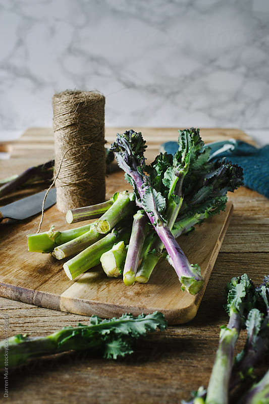 Purple sprouting broccoli on cutting board. by Darren Muir for Stocksy United