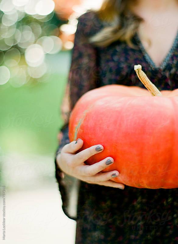 Girl with an orange pumpkin by Marta Locklear for Stocksy United