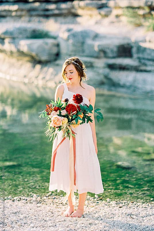 Vertical portrait of a lovely woman with a large bouquet outdoors by the water by Kristen Curette Hines for Stocksy United