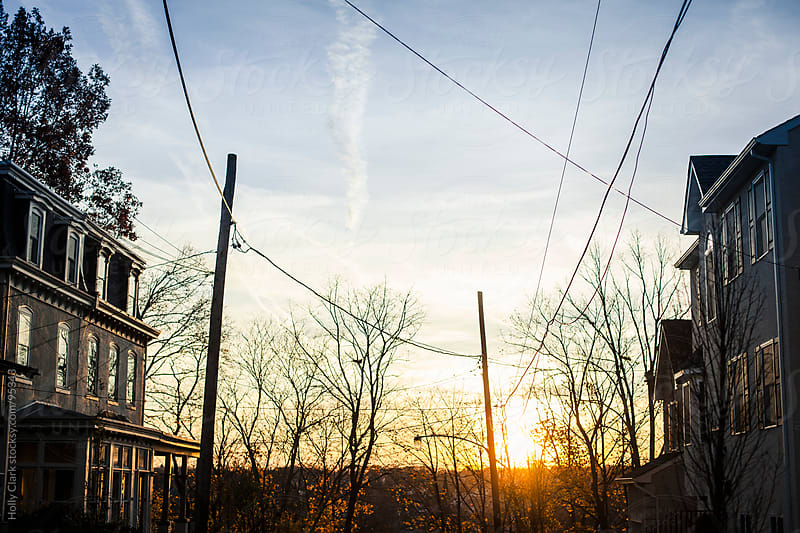 An autumn sunset over a Philadelphia neighborhood. by Holly Clark for Stocksy United
