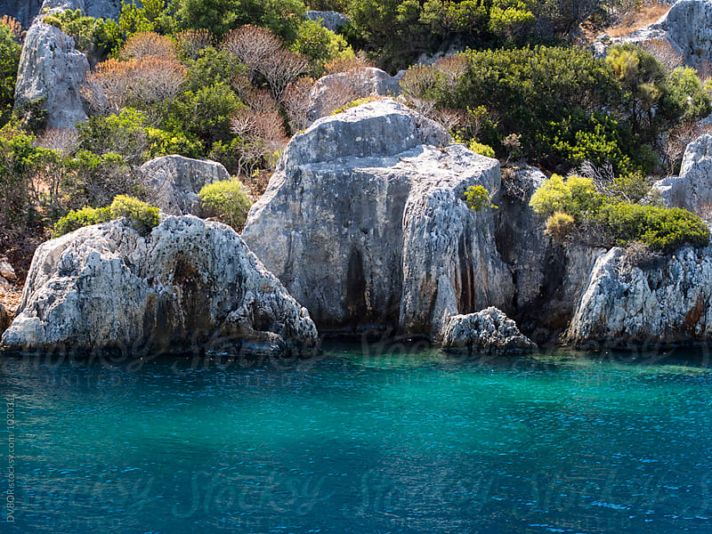 A rocky shoreline with crystal clear blue / green sea  by DV8OR for Stocksy United
