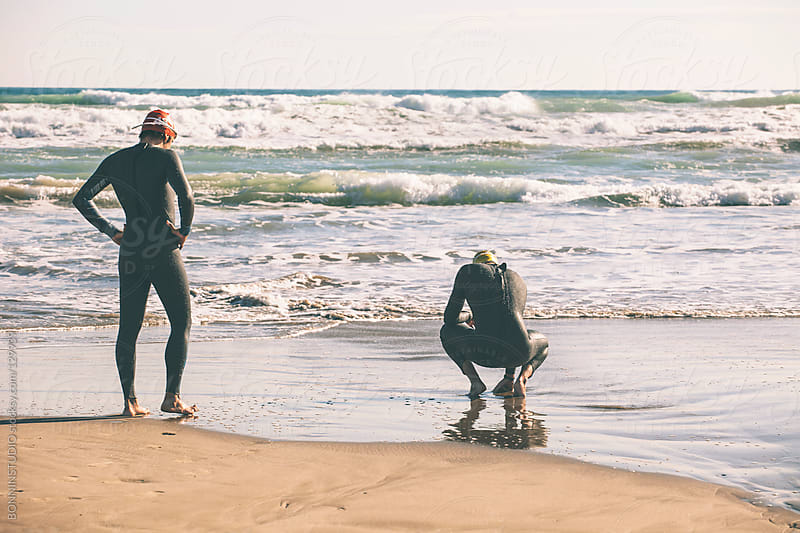 Two triathletes with wetsuit resting after triathlon race. by BONNINSTUDIO for Stocksy United