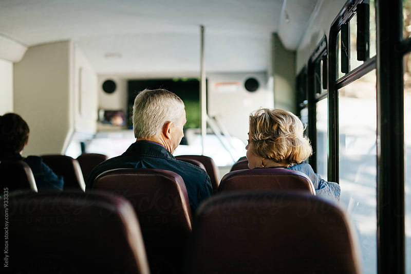 senior couple having conversation on a bus by Kelly Knox for Stocksy United