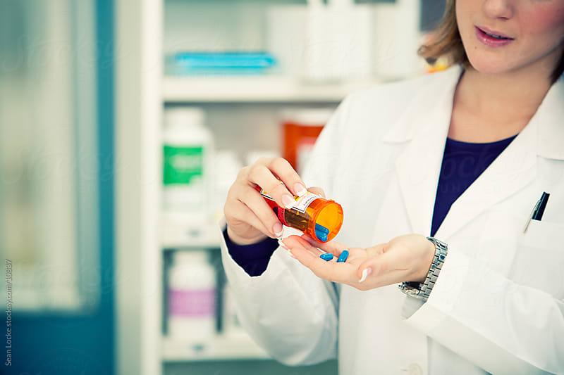 Pharmacy: Checking Medicine Inside Bottle by Sean Locke for Stocksy United