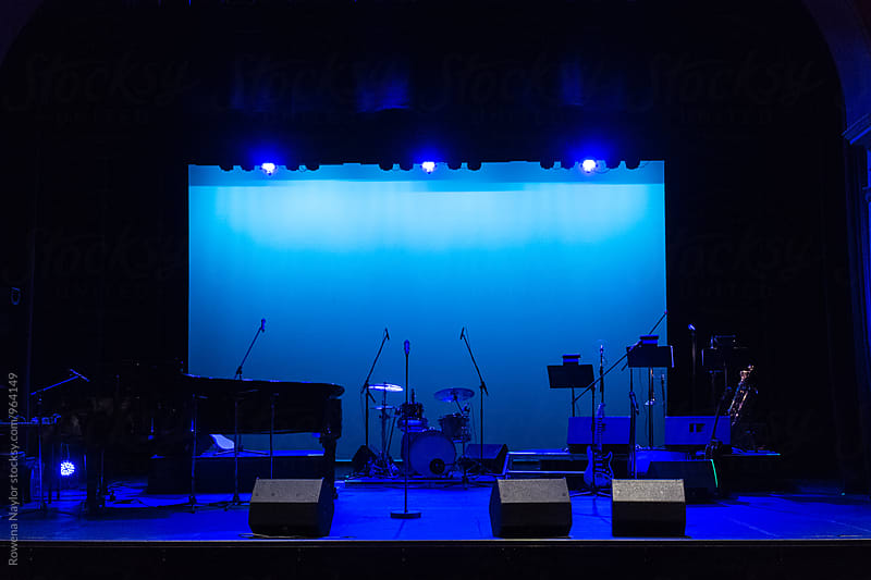 Empty concert stage bathed in blue light by Rowena Naylor for Stocksy United