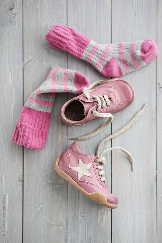 Pink toddler shoes on blue wood in pastel colours by Ina Peters for Stocksy United