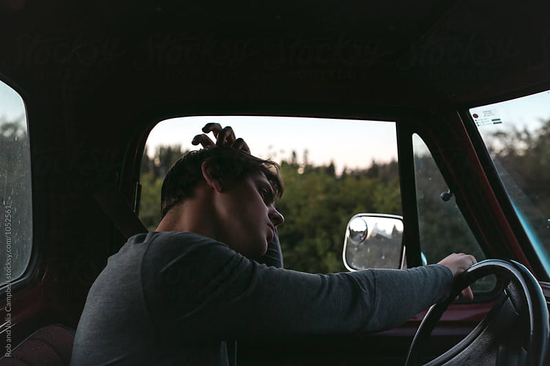 Young man enjoying summer road trip in old truck by Rob and Julia Campbell for Stocksy United