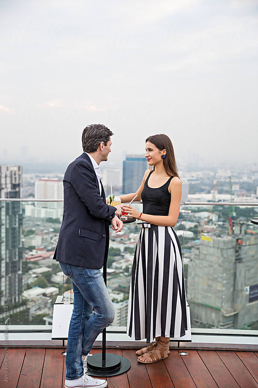 Fashionable young couple in love on a date in a modern rooftop bar overlooking the city  by Jovo Jovanovic for Stocksy United