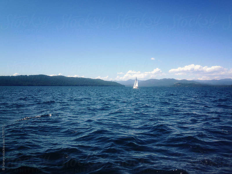 Sailboat on Blue Water in Front of Blue Mountains and Blue Sky by B. Harvey for Stocksy United