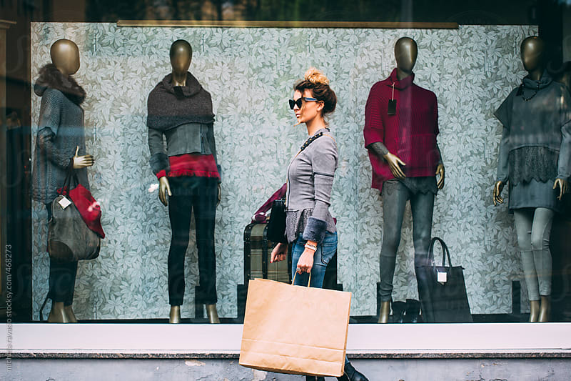 Woman walking next to window of a clothing store with a bag by michela ravasio for Stocksy United