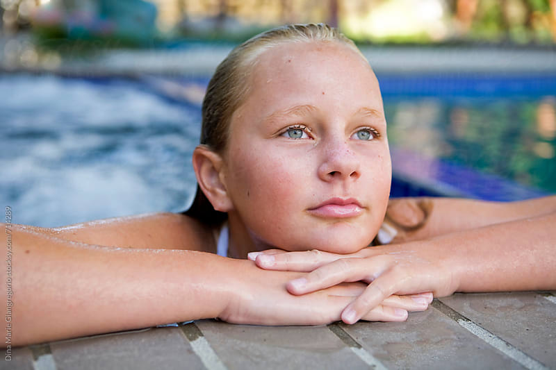 Blonde, Tan Teenager in Pool Resting On Edge by Dina Giangregorio for Stocksy United