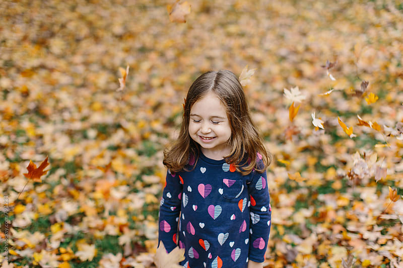 Cute young girl playing with leaves outside by Jakob for Stocksy United