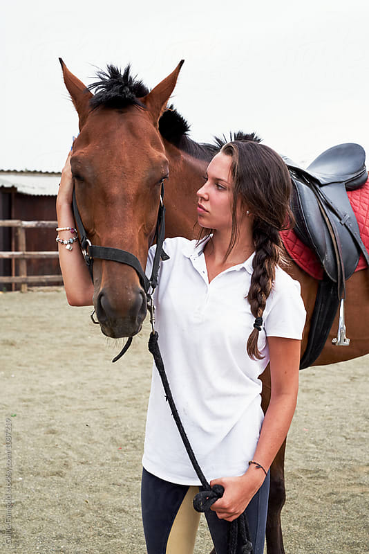 Teen brunette with her brown horse on paddock by Guille Faingold for Stocksy United