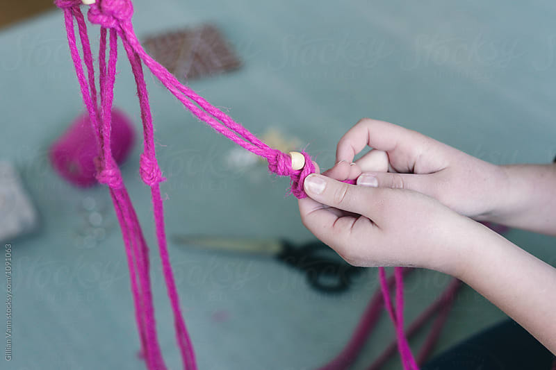 Macrame project, step 5: add beads by Gillian Vann for Stocksy United