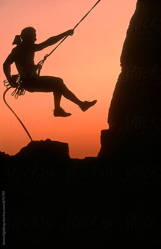 Silhouette of climber rapelling down a cliff face at sunset by Søren Egeberg Photography for Stocksy United