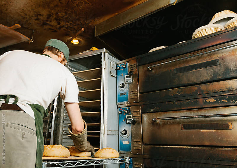 Baker checking freshly baked bread at a commercial artisinal bakery by Mihael Blikshteyn for Stocksy United