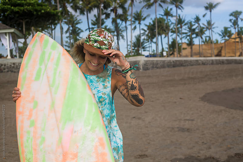 A beautiful tattooed surfer girl at the beach with her surfboard by Jovo Jovanovic for Stocksy United