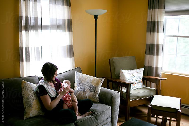 Mom feeding baby  by Jennifer Brister for Stocksy United