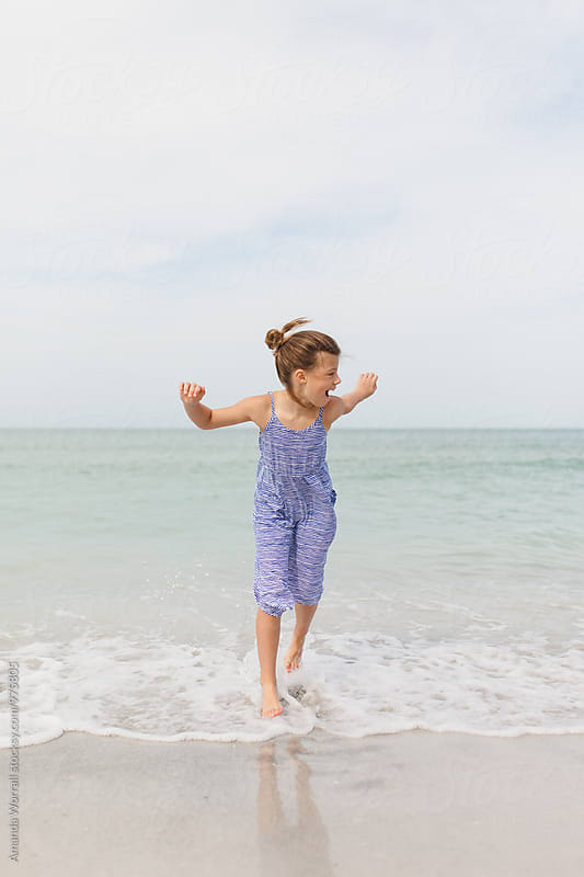 Preteen girl laughing while running in the ocean by Amanda Worrall for Stocksy United