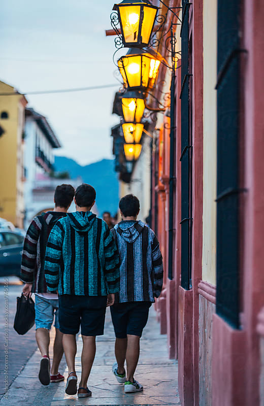 Group of three friends walking down the street of a colonial Mexican city at dusk with poncho sweaters by Alejandro Moreno de Carlos for Stocksy United