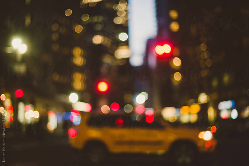 Blurred taxi cab driving through a city street at night by Lauren Naefe for Stocksy United