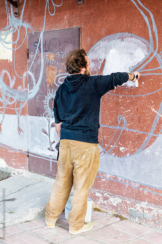Male graffiti artist painting on wall by Pixel Stories for Stocksy United
