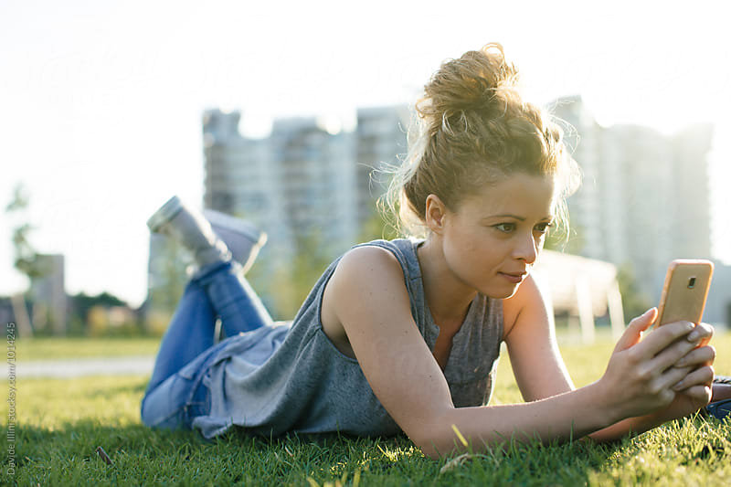 Young blonde woman using a phone outdoors by Davide Illini for Stocksy United