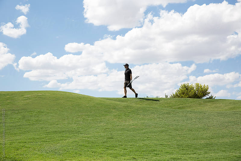 Man walking to putt in the clouds by Curtis Kim for Stocksy United