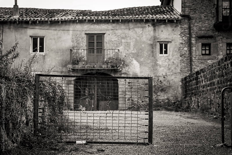 Old house with a fence made with a mattress by Marta Muñoz-Calero Calderon for Stocksy United