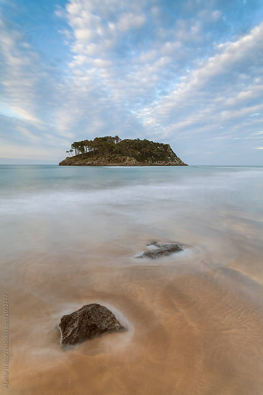 Low tide on a beach with a small island in the background by Marilar Irastorza for Stocksy United