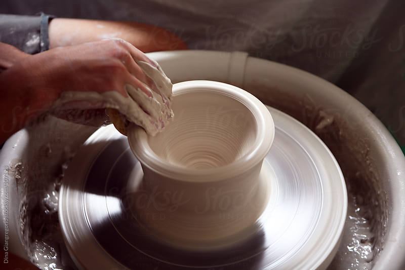 Ceramicist shaping the edges of bowl / cup using pottery wheel by Dina Giangregorio for Stocksy United