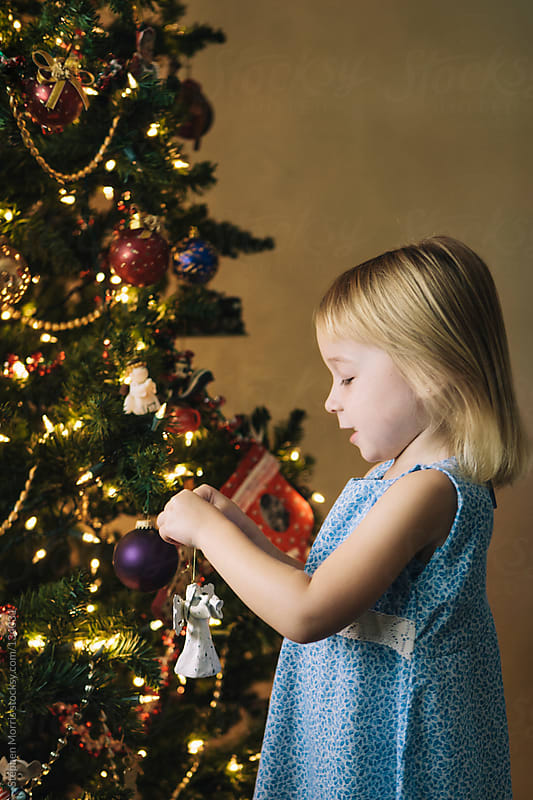 Little Girl Decorating Christmas Tree by Stephen Morris for Stocksy United