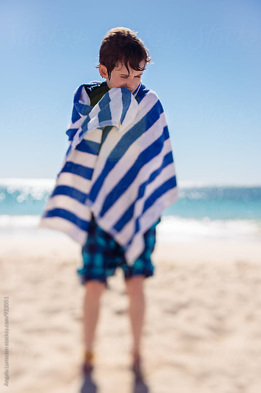 Boy wrapped in a blue and white striped towel at the beach  by Angela Lumsden for Stocksy United