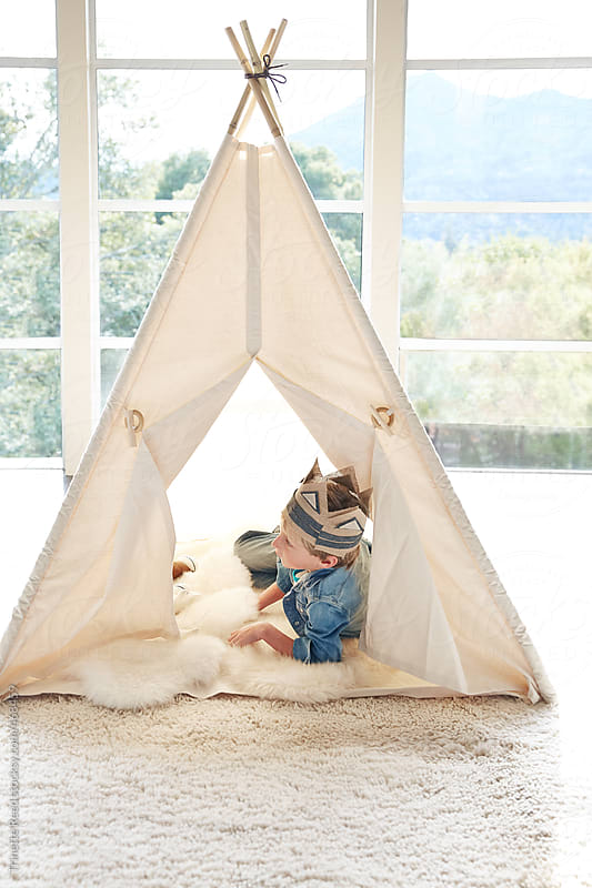 Little boy wearing costume playing in teepee tent in living room by Trinette Reed for Stocksy United