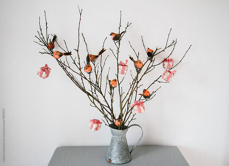 Branches decorated with little feathered robins and Christmas parcels by Helen Rushbrook for Stocksy United