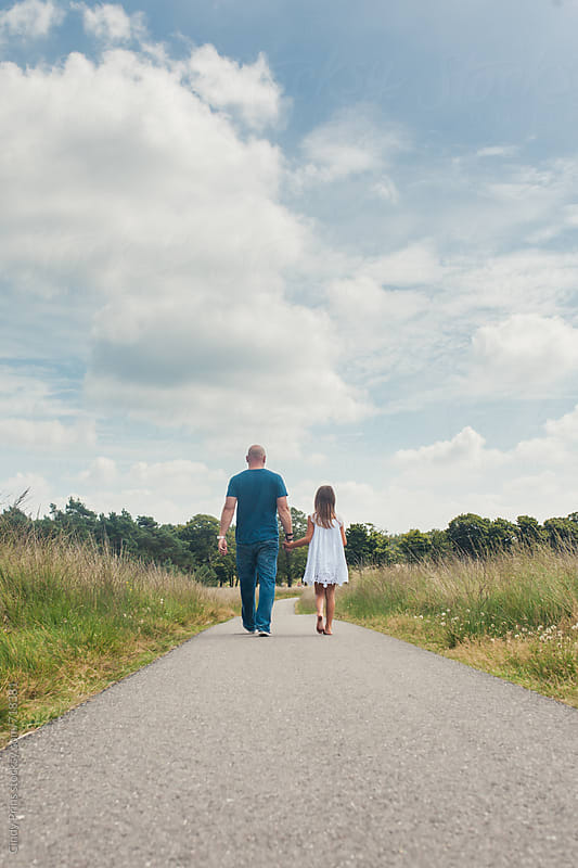 A little girl and her father holding hands and walking on a long road by Cindy Prins for Stocksy United
