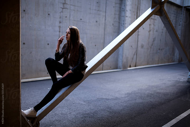 Sitting on a steel beam and having a cigarette  by MEM Studio for Stocksy United
