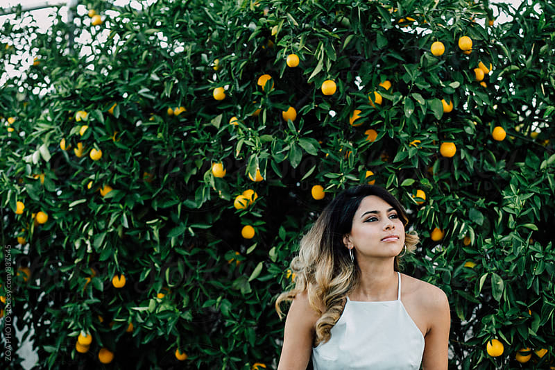 Portrait of a woman in front of an orange tree by ZOA PHOTO for Stocksy United